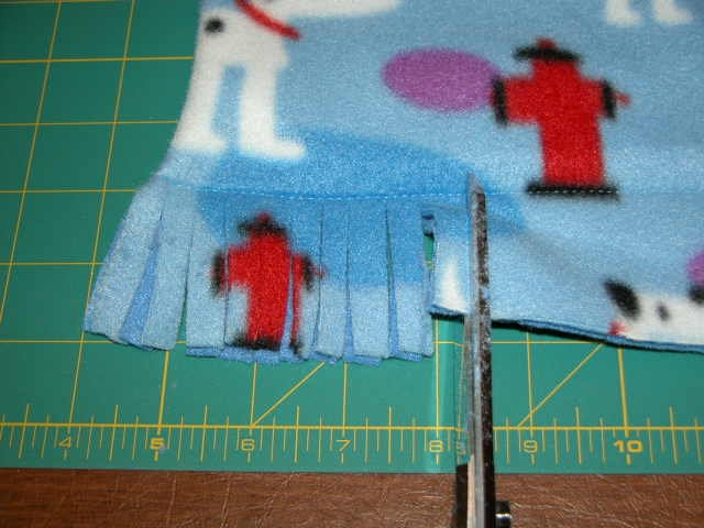 Adding fringe to a blanket.